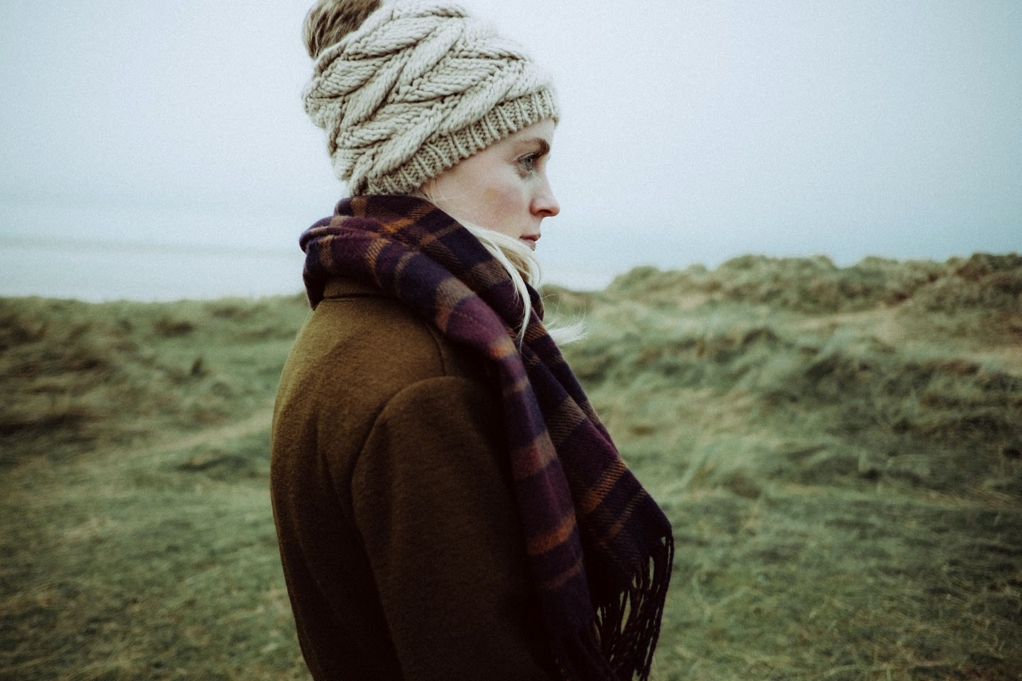 woman in winter clothing standing in a grassy field